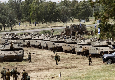 Israeli soldiers walk by tanks during a military drill in the Golan Heights
