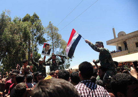 Residents celebrate the army's arrival in the formerly rebel-held town of Ibta, northeast of Deraa city, Syria