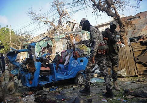 Somali soldiers stand near damaged vehicles after a car bomb for which al-Shabaab took responsibility