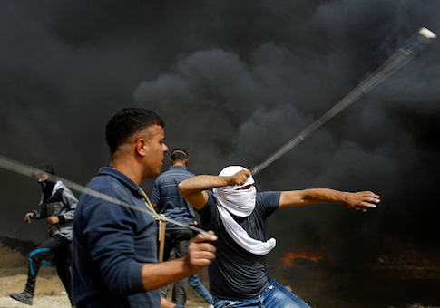 Palestinian protestors uses slings to throw stones towards Israeli forces during clashes across the border, following a demonstration calling for the right to return