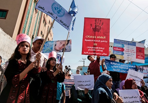 UNRWA staff take part in a protest in front of the agency's headquarters in Gaza City