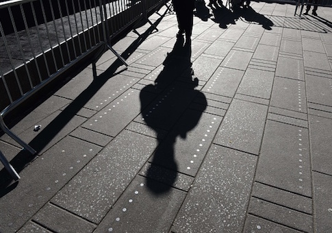 Shadow of a NYPD officer during a press conference on new barriers to prevent terror attacks