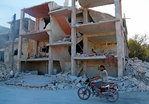 A Syrian man rides a motorcycle past a destroyed building in the district of Jisr al-Shughur, in the Idlib province