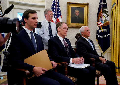 FILE PHOTO: White House aides look on as Trump announces deal on NAFTA at the White House in Washington