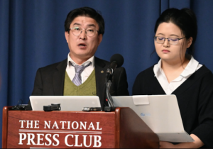 North Korean former overseas worker, Roh Hui-Chang (left), with a translator