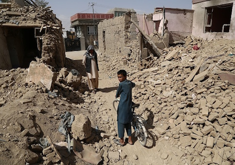 Afghan residents walk near destroyed houses after a Taliban attack in Ghazni