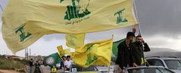 A supporter of Lebanon's Hezbollah gestures as he holds a Hezbollah flag in Marjayoun