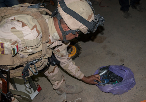 An Iraqi Army soldier inspects a bag of electronic components in a drone and IED factory