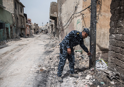 An Iraqi federal police captain points towards an unexploded IED left by ISIS