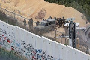 Israeli soldiers gathering by an army vehicle across the concrete Lebanon-Israel border wall near the site of an Israeli excavation site