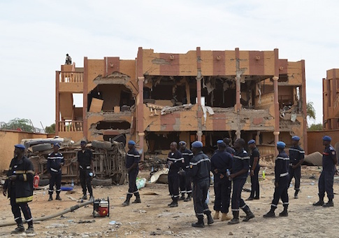 A Malian firefighters stand beside a destroyed building in Gao, after a suicide car bomb attack