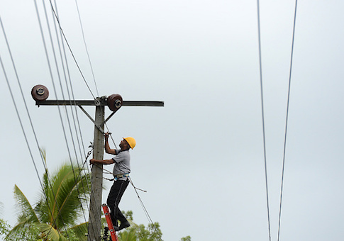 A worker is seen on top of an utility pole