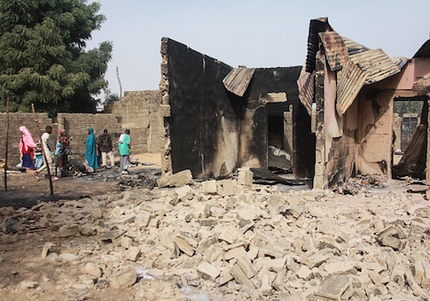 A group of children walk past rubbles and remains of a house following a Boko Haram attack