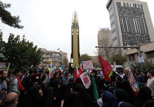 Iranians gather next to a replica of a Ghadr medium-range ballistic missile