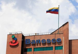 A Venezuelan flag waves above the corporate logo of Banesco bank at one of their office complexes in Caracas