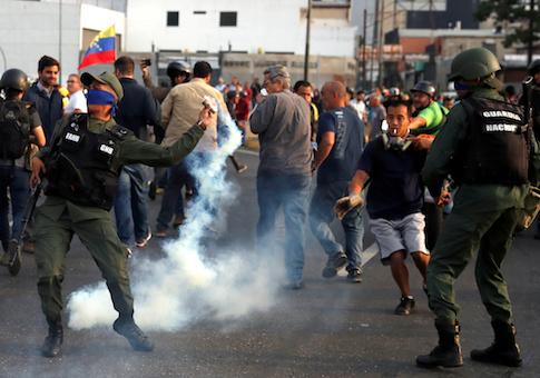 "A military member throws a tear gas canister near the Generalisimo Francisco de Miranda Airbase ""La Carlota"", in Caracas, Venezuela"