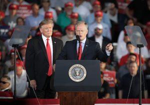 President Donald Trump looks on as Fred Keller speaks