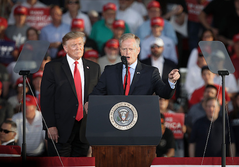 President Donald Trump looks on as Fred Keller speaks