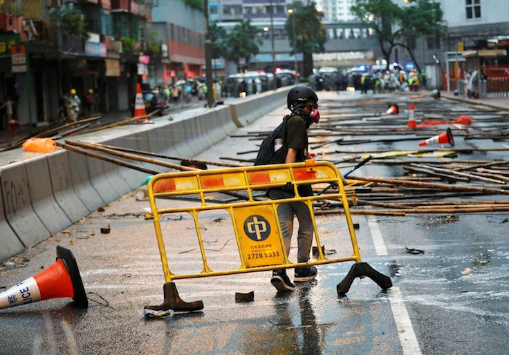 An anti-extradition bill protester carries a barricade for blocking the road during a protest in Hong Kong