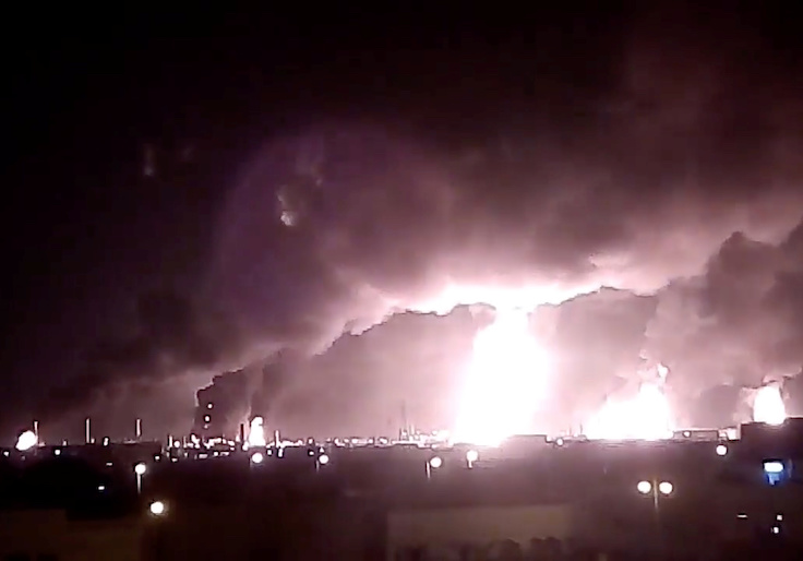 Fires burn in the distance after a drone strike by Yemen's Iran-aligned Houthi group on Saudi company Aramco's oil processing facilities, in Buqayq, Saudi Arabia