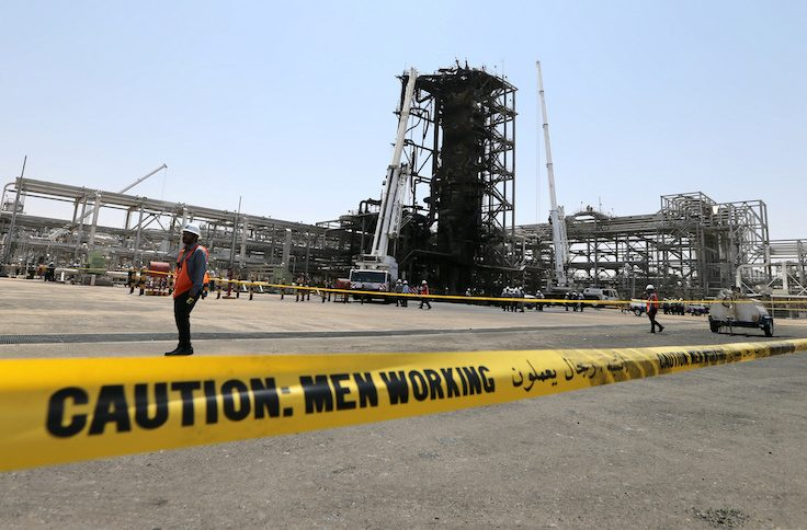Workers are seen at the damaged site of Saudi Aramco oil facility in Khurais, Saudi Arabia