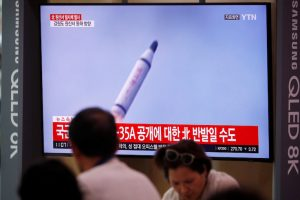 People watch a TV screening of a file footage for a news report on North Korea firing a missile that is believed to be launched from a submarine, in Seoul, South Korea