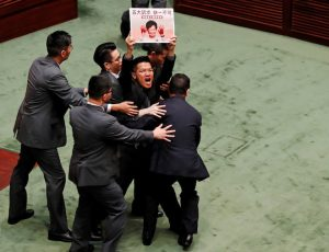 A pro-democracy lawmaker holding a placard is escorted by security from the Legislative Council