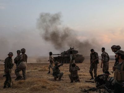 Turkish soldiers and Turkey-backed Syrian fighters gather on the northern outskirts of the Syrian city of Manbij near the Turkish border