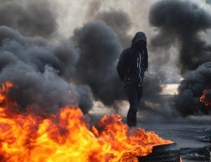 An Iraqi demonstrator walks next to burning tires blocking a road, during ongoing anti-government protests, in Kerbala