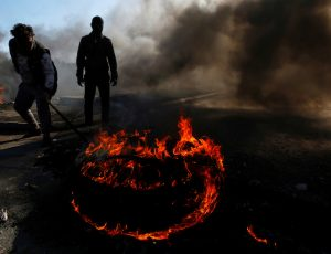 Iraqi demonstrators burn tires to block a road during ongoing anti-government protests in Najaf