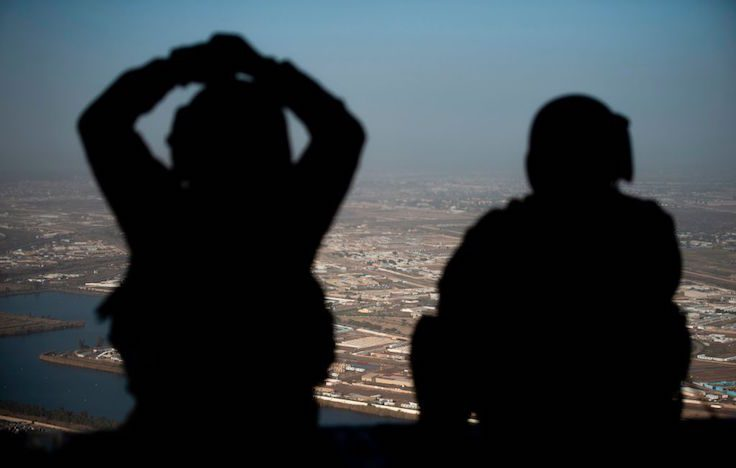 U.S. Army helicopter crew members look out of their Chinook helicopter as they fly from the U.S. Embassy to Baghdad International airport