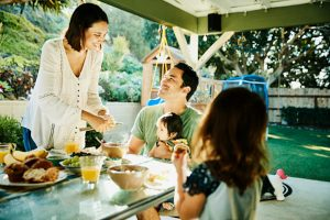 Smiling mother and father sharing breakfast with young family at table in backyard