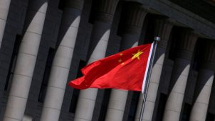 Chinese flag flutters in front of the Great Hall of the People in Beijing