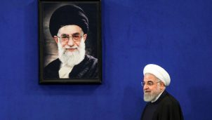 Iranian President Hassan Rouhani walks past a portrait of Supreme Leader Ayatollah Ali Khamenei