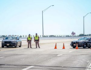 Florida State Troopers block traffic over the Bayou Grande Bridge leading to the Pensacola Naval Air Station
