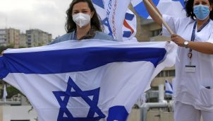 Medical professionals at Ziv Medical Centre wave Israeli national flags