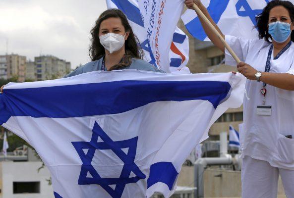 Medical professionals at Ziv Medical Centre wave Israeli national flags