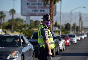 A Nevada Highway Patrol officer directs vehicles as they wait to get into a drive-thru food distributing site