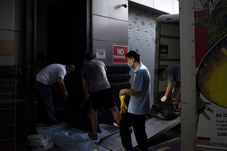 People move trash bags from the Chinese consulate in Houston on July 24