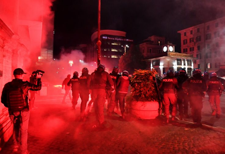 Italian police officers clash with protesters during a protest against the government restriction measures to curb the spread of COVID-19