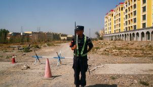 A Chinese police officer takes his position by the road near what is officially called a vocational education center in Yining in Xinjiang Uighur Autonomous Region, China
